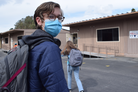 Connor Lassila (sophomore) walks to his next class outside the science building while wearing a mask. Paly requires all students to wear a mask while on campus. Photo: Anya Lassila.