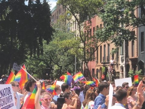 2019 New York Pride parade attendees walk down the street waving rainbow flags. Photo by Ash Mehta
