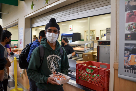 """Senior Ronak Momga picks up a free meal from the cafeteria during the lunch period. Students are expressing their overall content with the new statewide free lunch program, despite a few complaints regarding the actual food. The impact of the program on lower-income students is proving to be a significant aspect of the free lunches. """"Even though it [the free lunch program] is not the best, I'm happy with it,"""" junior Audrey Guo said."""